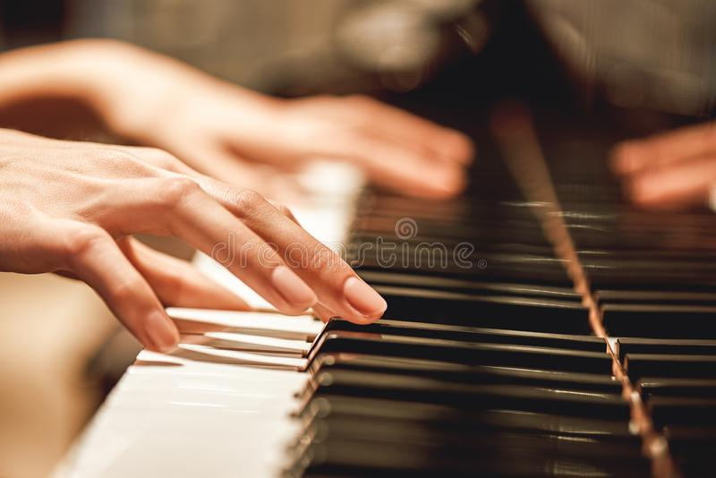 Beautiful Piano Melody...Close up view of female hands playing on piano her favorite classical music. Musical instrument. Music education. Piano keyboard stock image