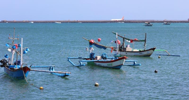 Beautiful picture of fishing boats at Jimbaran Bay at Bali Indonesia, beach, ocean, fishing boats and airport in photo. stock photos