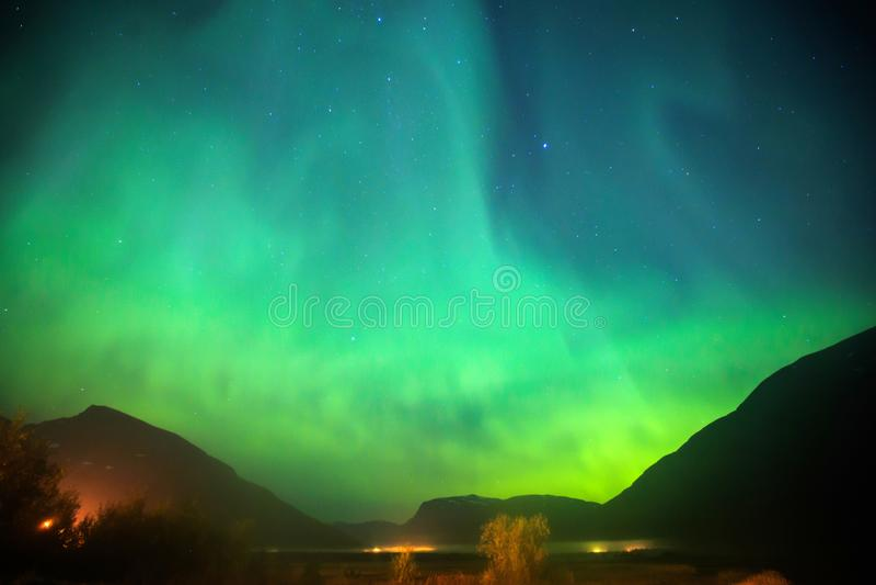 Beautiful picture of massive multicolored green vibrant Aurora Borealis, Aurora Polaris, also know as Northern Lights in Norway stock photo