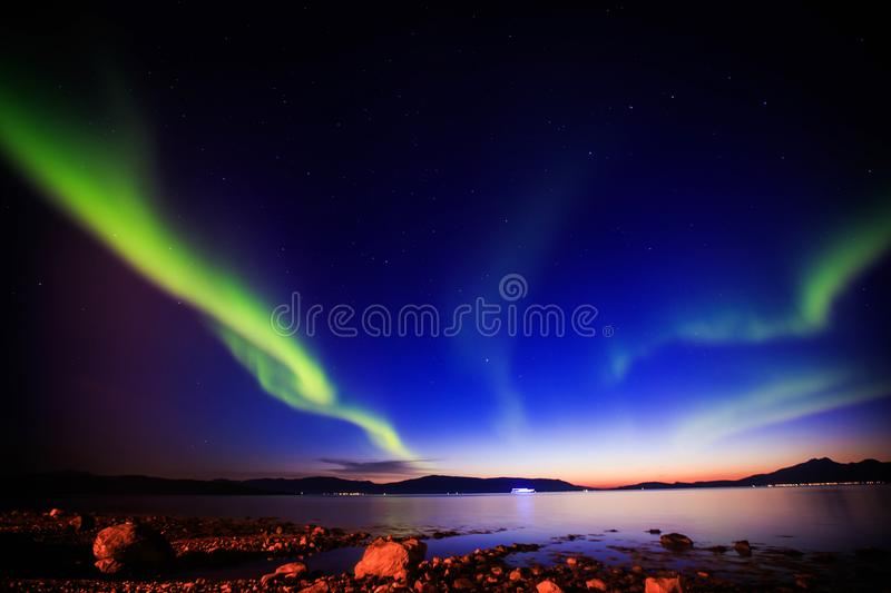 Beautiful picture of massive multicolored green vibrant Aurora Borealis, Aurora Polaris, also know as Northern Lights in Norway stock photography