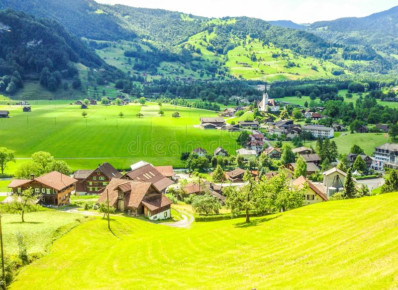 Beautiful, picturesque, stunning summer day view of Lungern Village surrounding its Pfarrkirche Catholic Church from train window royalty free stock images