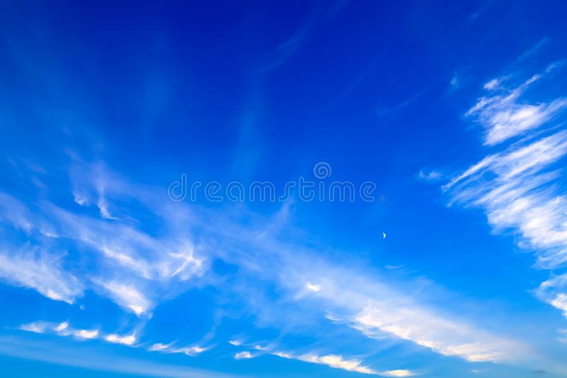 Beautiful picturesque white feather clouds on the blue sky with a young moon , magic romantic background. Beautiful picturesque white feather clouds on the dark royalty free stock image