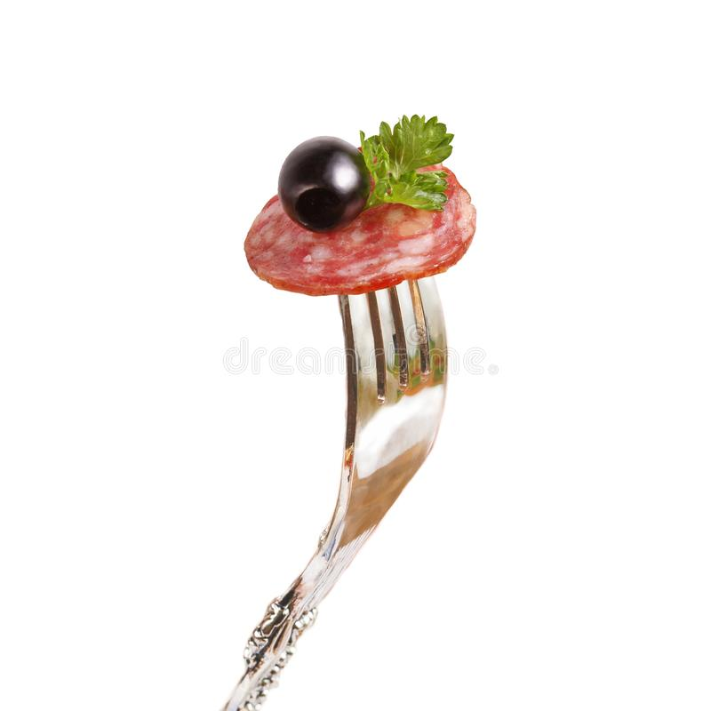 A beautiful piece of smoked sausage with olive and parsley pinned on a fork. stock photos