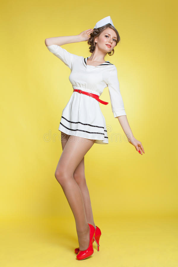 beautiful pin up girl dressed a sailor posing on yellow background wall stock photo image. Black Bedroom Furniture Sets. Home Design Ideas