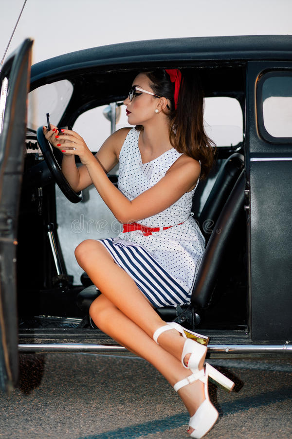Beautiful pin-up girl inside vintage car watching mirror.  stock photo