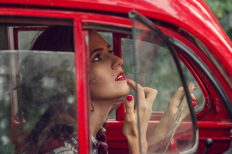 A beautiful pin-up girl in a plaid shirt corrects make-up in the salon of an old red retro car. stock images