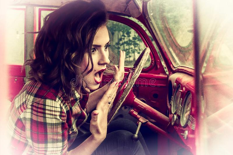 Beautiful pin-up girl in a plaid shirt is frightened and screaming, looking at the speedometer in the cabin of royalty free stock photos
