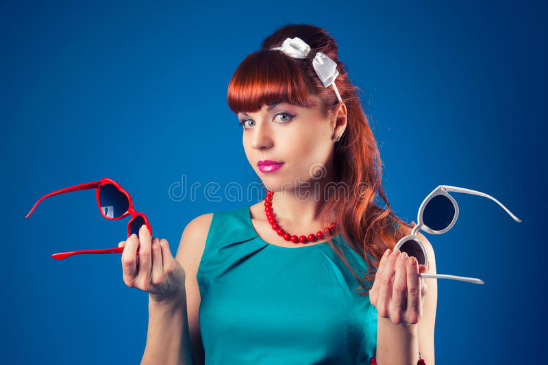 beautiful pin-up girl posing with two pairs of sunglasses against blue background stock photography