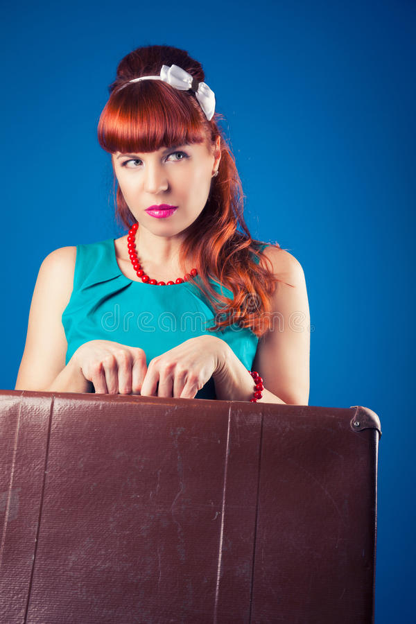 Beautiful pin-up girl posing with vintage suitcase against blue stock photo