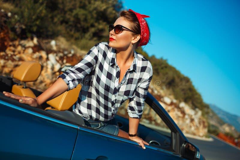 Beautiful pin up woman sitting in cabriolet, enjoying trip on lu stock photo