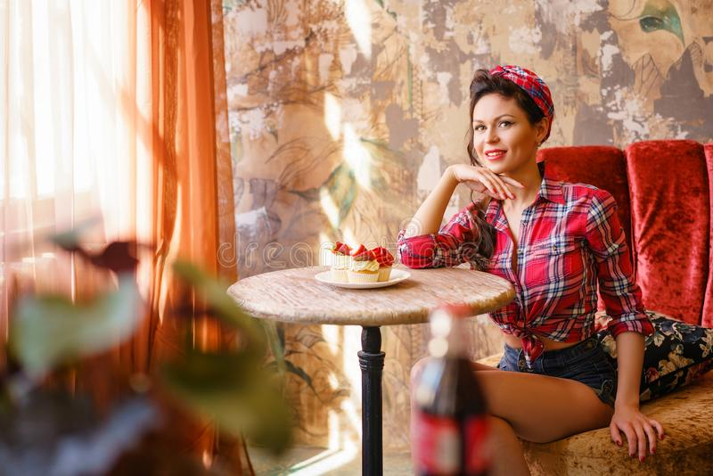 Beautiful pin-up woman sitting at a table in a cafe stock image
