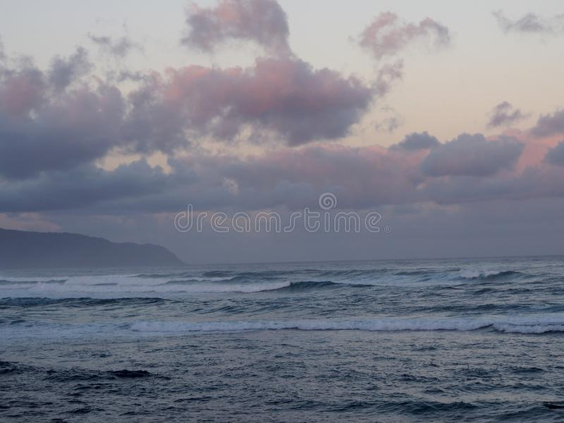 Beautiful pink and purple Dawn over the ocean with waves rolling stock photos