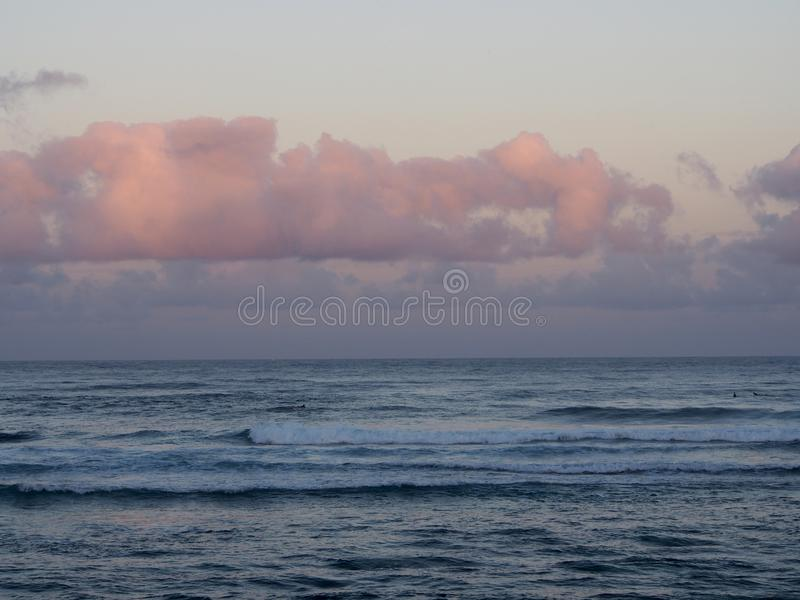 Beautiful pink and purple Dawn over the ocean with waves rolling. Towards the shore on the North Shore of Oahu with surfers in the water stock photography