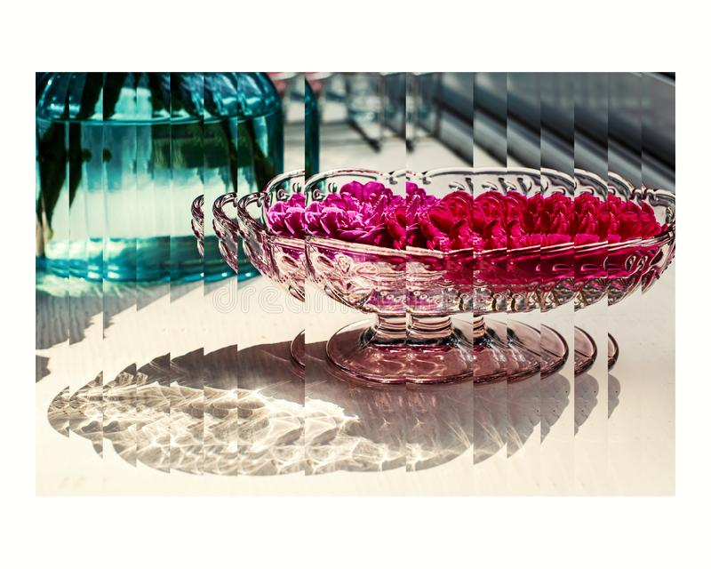 Beautiful pink and red flowers in clear glass vase with beautiful reflecting lighting on the table. Created in a radial style royalty free stock photo