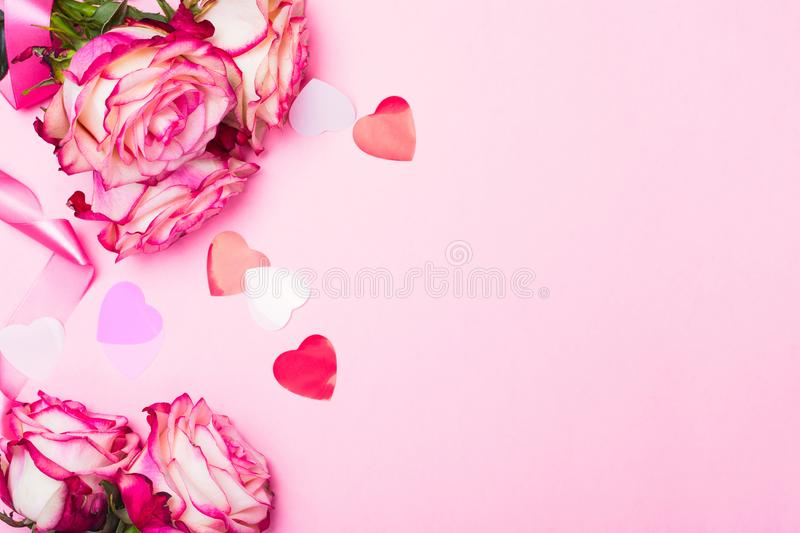 Beautiful pink rose, decorative confetti hearts and pink ribbon on pink Valentines day background. Copy space stock photos