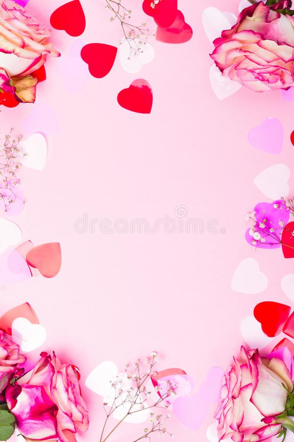 Beautiful pink rose, decorative confetti hearts and pink ribbon on pink Valentines day background. Copy space royalty free stock photos
