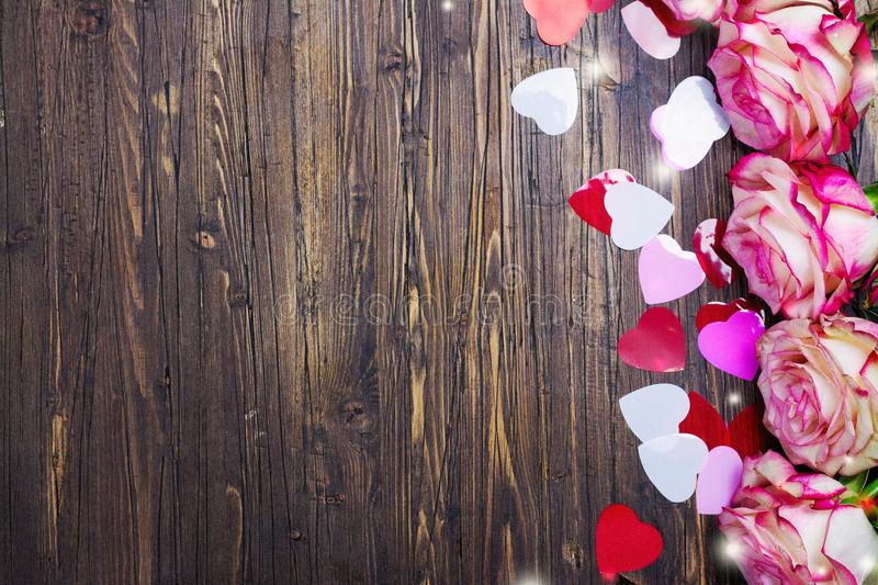 Beautiful pink rose, decorative confetti hearts on Valentines day background stock photos