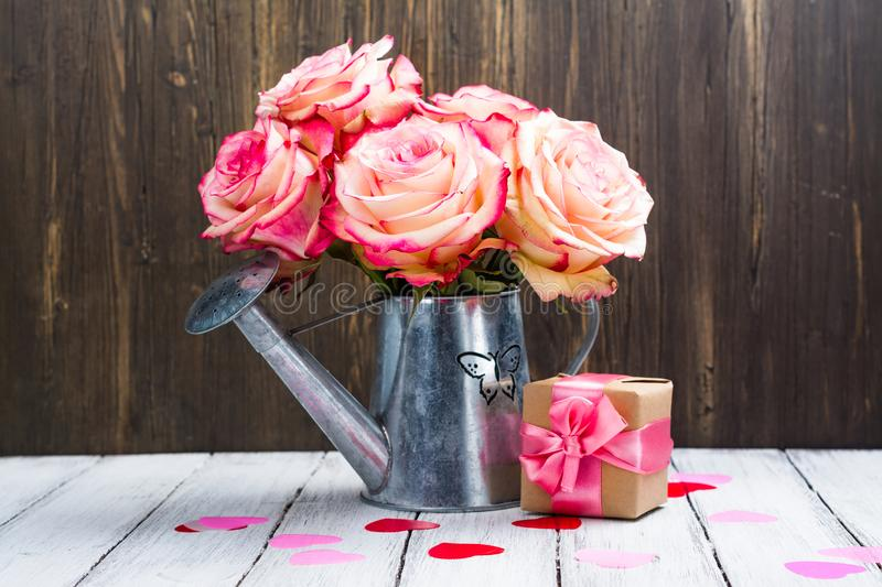 Beautiful pink rose in a tin watering can on wooden background stock photography