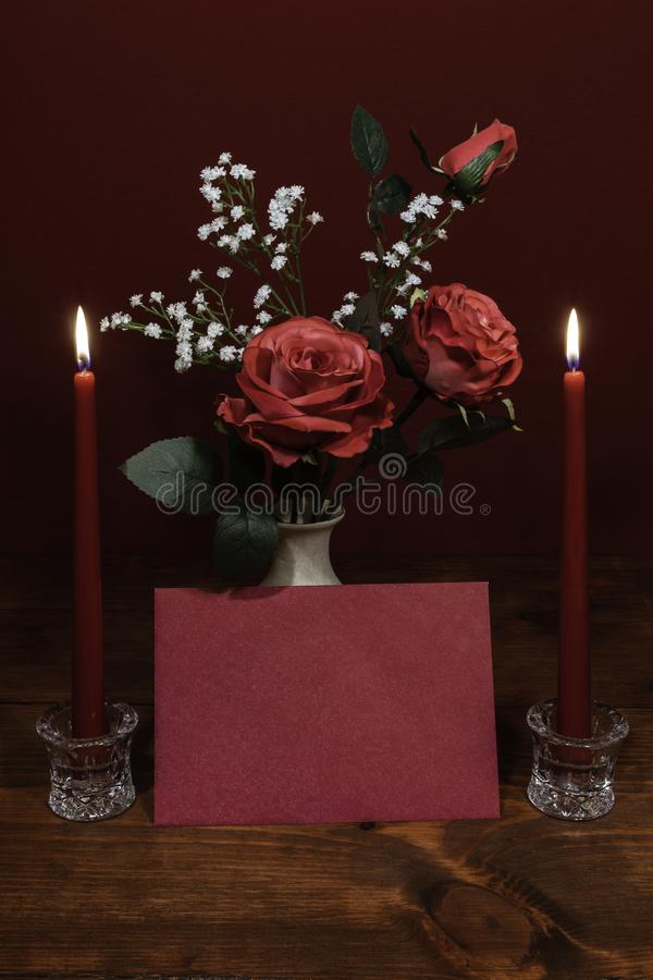 Beautiful pink roses in a vase accented with Baby`s Breath flowers, Two lit ed candles in crystal holder and a card. stock photos