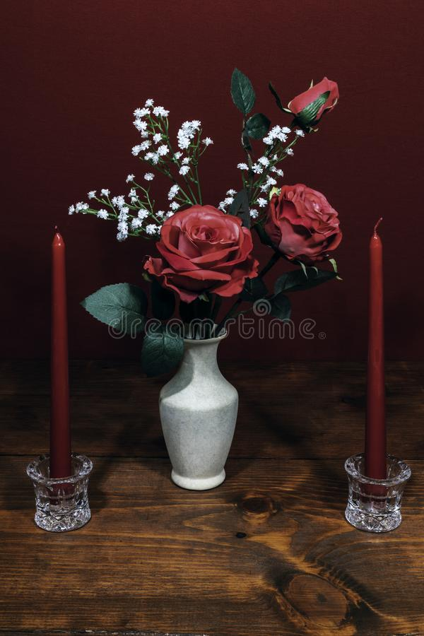 Beautiful pink roses in a vase acsented with Baby`s Breath flowers, Two red candles in crystal holder royalty free stock images