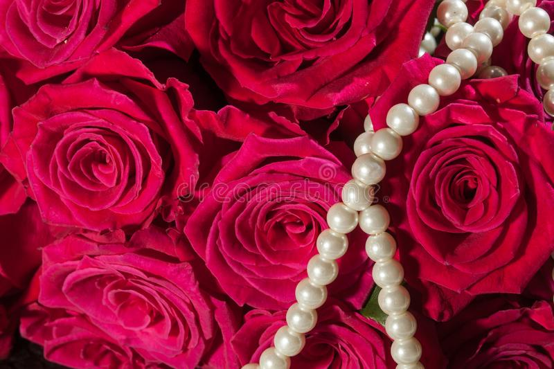 Beautiful pink roses and white pearls. Concept of beauty for women royalty free stock photo