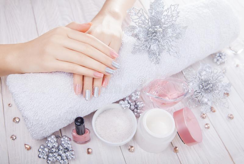 Beautiful pink and silver Christmas manicure with spa essentials royalty free stock photo