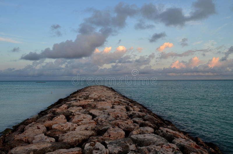 Beautiful Pink Skies Over a Rock Jetty in Aruba stock photo