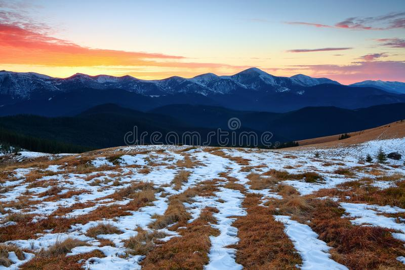 Beautiful pink sunset shine enlightens the picturesque landscapes with fair yellow grass and high mountains. stock images