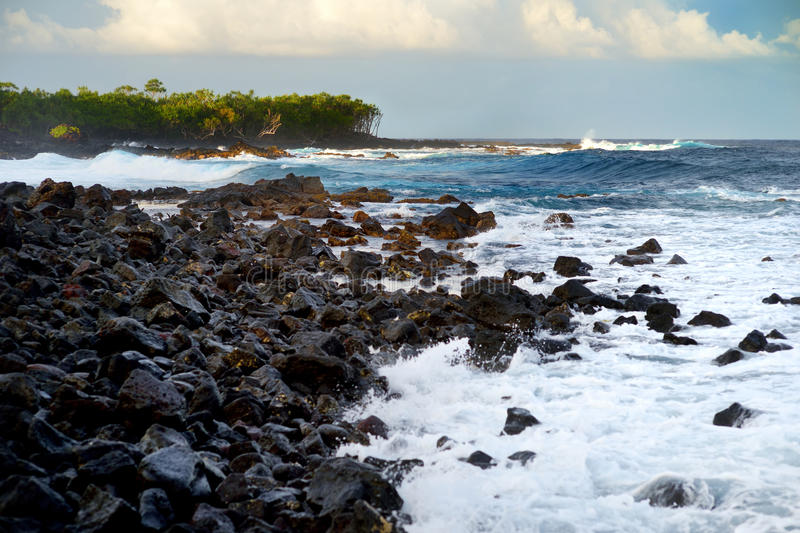 Beautiful pink tinted waves breaking on a rocky beach at sunrise on east coast of Big Island of Hawaii stock photography
