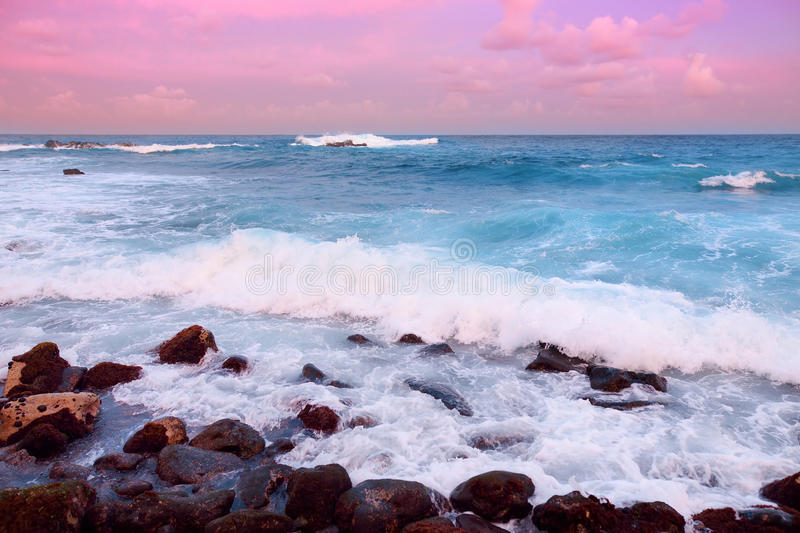 Beautiful pink tinted waves breaking on a rocky beach at sunrise on east coast of Big Island of Hawaii royalty free stock photography