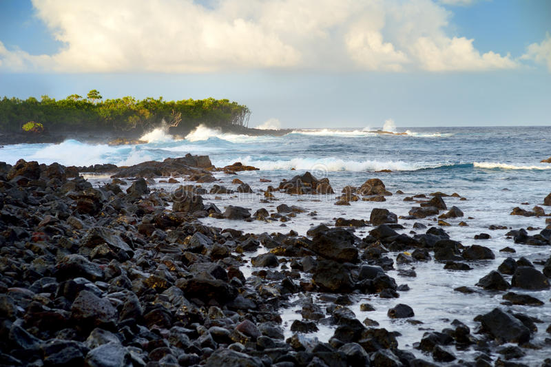Beautiful pink tinted waves breaking on a rocky beach at sunrise on east coast of Big Island of Hawaii royalty free stock images