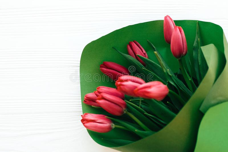 Beautiful pink tulips bouquet in green paper on white wooden background, top view. Happy mothers day. Red tulips close up on white stock images