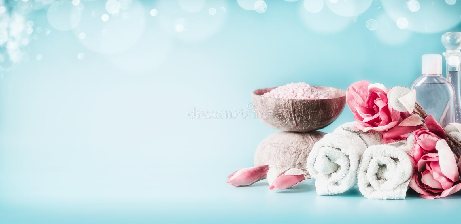 Beautiful pink white spa setting with towels, flowers, candles, sea salt and body care cosmetics at light blue background with royalty free stock image