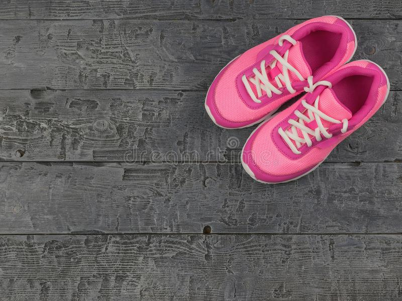 Beautiful pink women`s running shoes dark vintage on the floor. The view from the top. The concept of healthy lifestyle and sports stock image