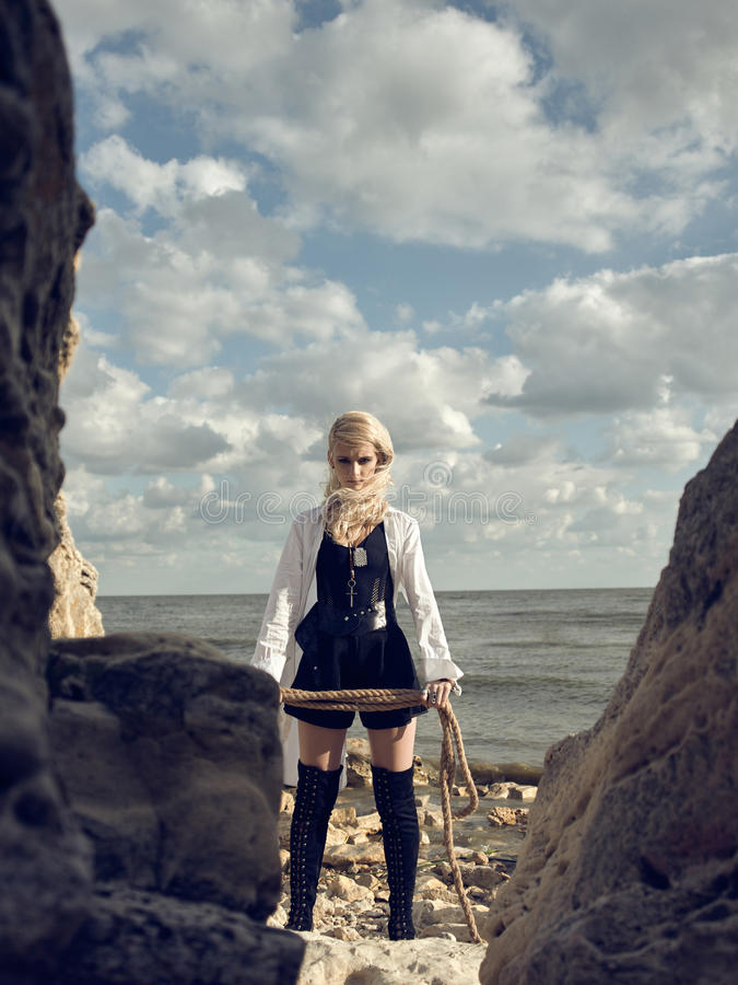 Beautiful pirate woman standing on the beach in boots. royalty free stock photos