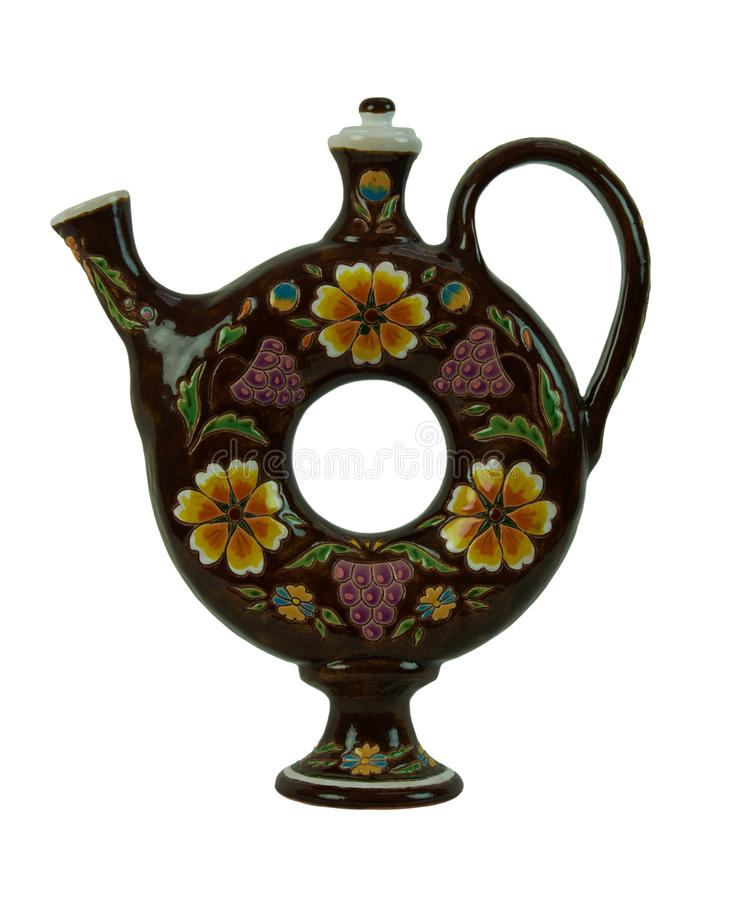 Beautiful pitcher for beverages in the form of a torus isolated. Pitcher for beverages in the form of a torus - pottery handmade from clay. Pitcher brown stock images