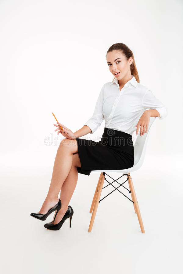 Beautiful playful businesswoman sitting on the chair and holding pencil stock photo