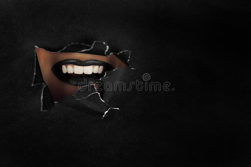 Beautiful plump, bright lips of black color drop into the slit of colored paper. Cosmetics, makeup, beauty salon, makeup artist, l. Ip gloss, beautiful teeth royalty free stock images
