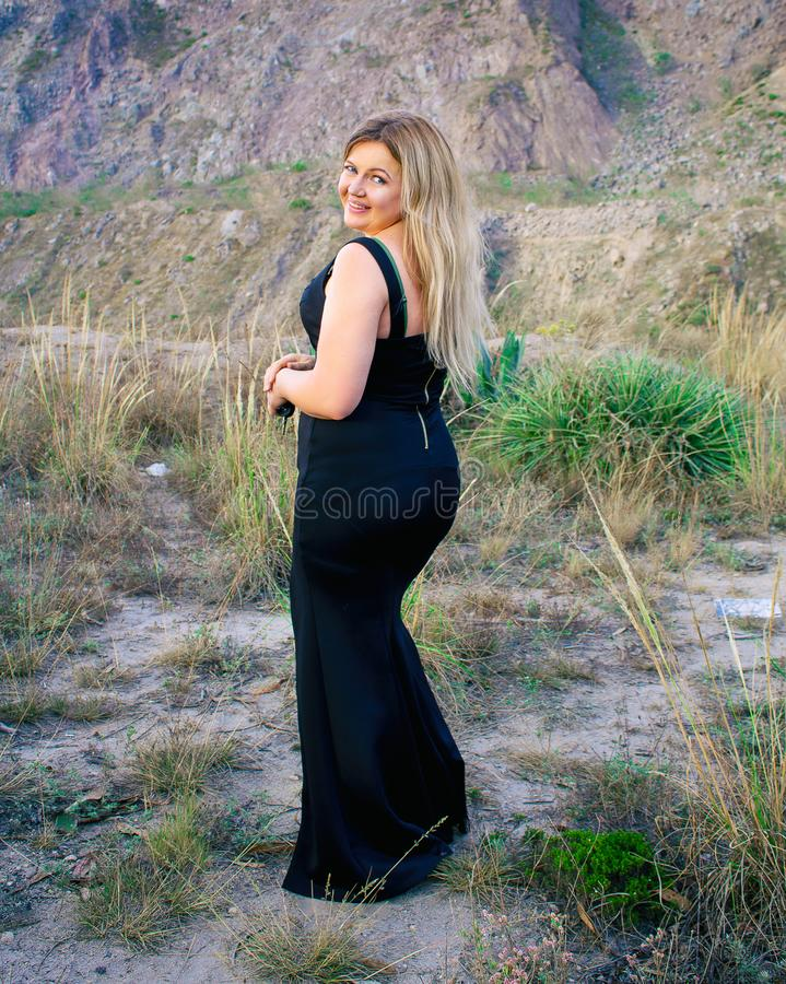 Beautiful plump woman in a black dress. Blonde. With a beautiful smile. Outdoors on a prairie. royalty free stock images