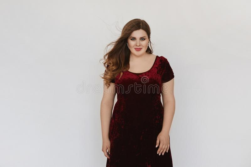 Beautiful plus size model girl in modish red velvet dress isolated at white background. Young fat woman with bright royalty free stock image
