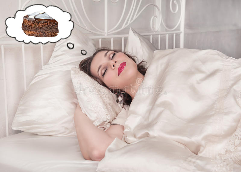 Beautiful plus size woman dreaming about cake. Beautiful plus size woman sleeping in the bed dreaming about cake royalty free stock image