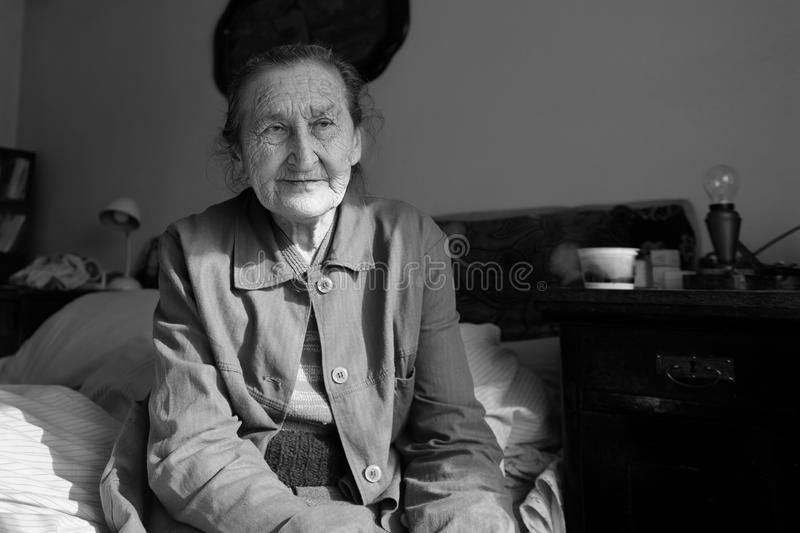 Beautiful 80 plus year old senior woman portrait. Black and white image of elderly worried woman sitting on a bed. royalty free stock photography