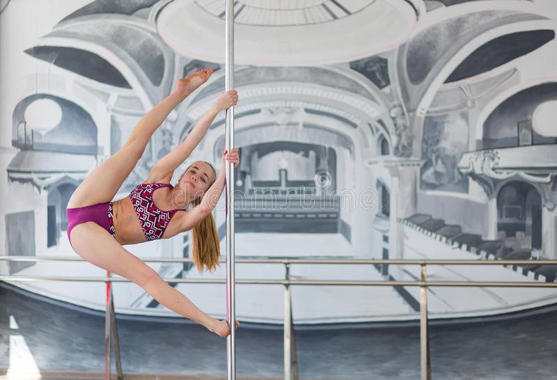 Beautiful pole dancer. Performing in a pole dance studio royalty free stock image