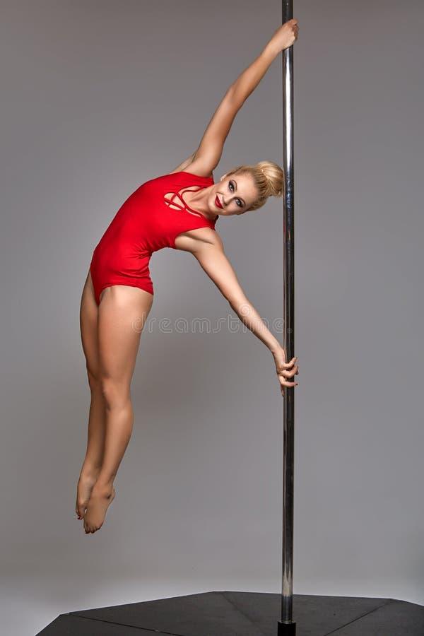 Beautiful pole dancer in red bodywear on pylon royalty free stock photo