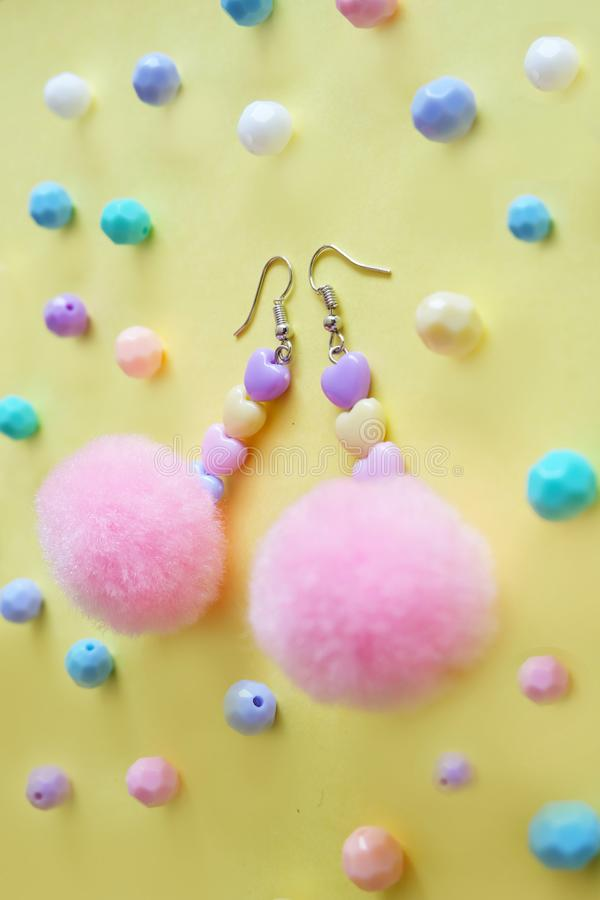 Beautiful Pom Earring Fashion Accessories. A Pair of Earring with Pink Circle Beads Isolated on Yellow Bead Background. Great For Any Use royalty free stock image