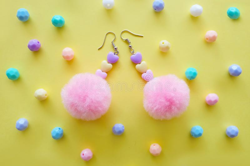 Beautiful Pom Earring Fashion Accessories. A Pair of Earring with Pink Circle Beads Isolated on Yellow Bead Background. Great For Any Use royalty free stock photos