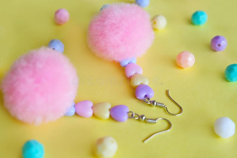 Beautiful Pom Earring Fashion Accessories. A Pair of Earring with Pink Circle Beads Isolated on Yellow Bead Background. Great For Any Use stock photo