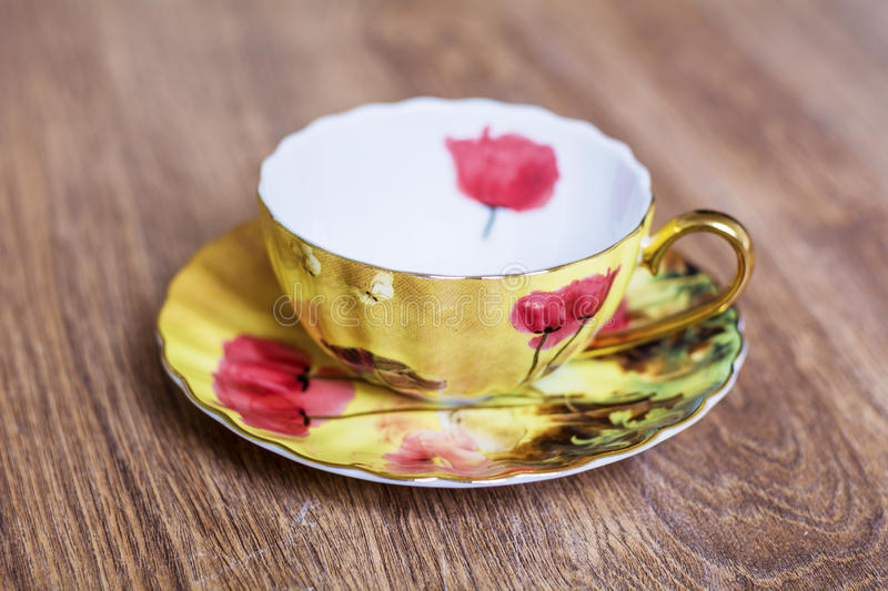 Beautiful porcelain cup. Golden porcelain cup with red poppies stock photography