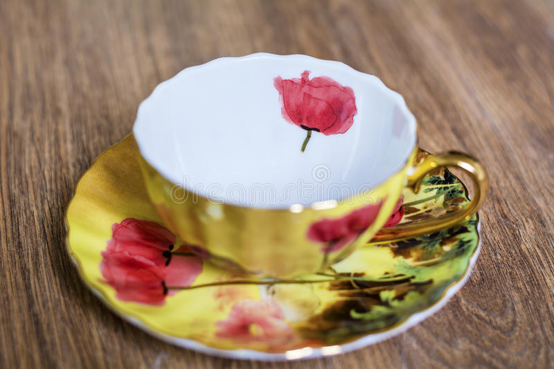 Beautiful porcelain cup. Golden porcelain cup with red poppies stock photos