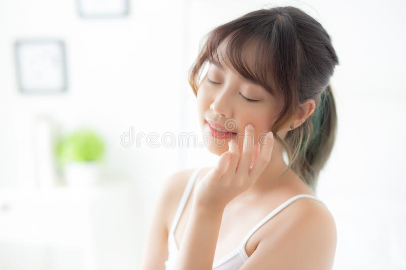 Beautiful portrait asian woman makeup of cosmetic, girl hand touch cheek and smile attractive. Face beauty perfect with wellness in the bedroom with skin care royalty free stock photos